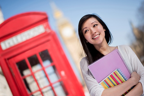 Asian exchange student in London thinking and holding notebooks - education concepts