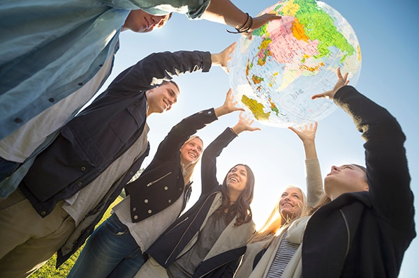 Group of people holding a world globe outdoors