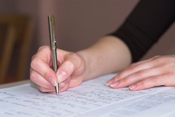 Female student is taking test in math. Fingers in focus.