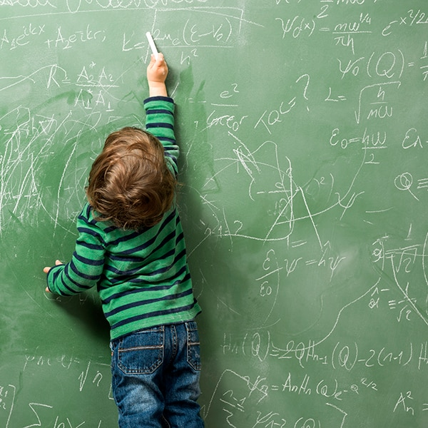 Little boy writing on green blackboard with math formulas written on.He is wearing a rgreen sweater and standing on the left side of frame.The green board is full of mathematics and physics formulas.He is seen in full length and holding chalk in left hand.The photo was shot in studio with a medium format camera Hasselblad H4D.
